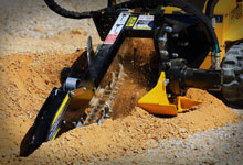 Compact loader digging with a Digga Mini Bigfoot Trencher.