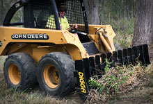 Skid steer loader with a Root Rake.