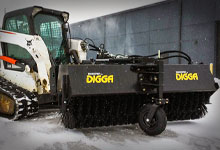 Tracked loader with a Digga Sweeper Broom in the snow.
